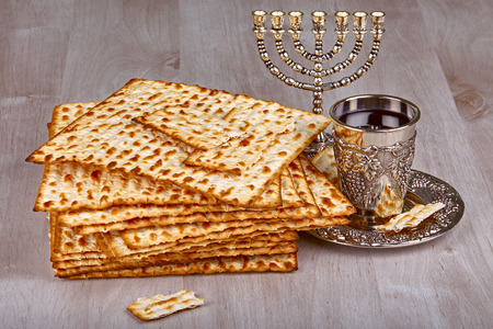 pesah: passover matzo with kiddush cup of wine on wooden table