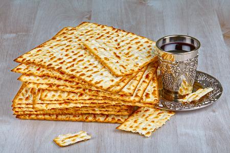 matzah: Closeup of Matzah with kiddush cup of wine on wooden table