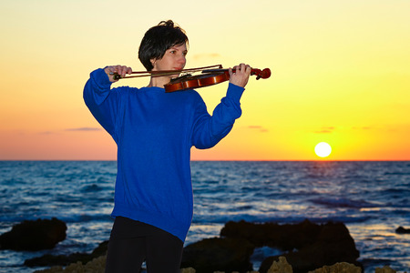 a young beautiful brunette woman music lover on beach with a violin at sunset photo