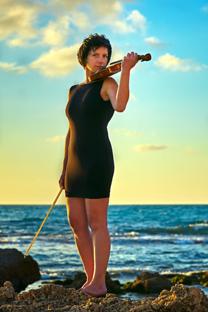 brunette woman music lover on beach with a violin at sunset photo