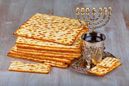 pesakh: passover matzo (jewish passover bread) with kiddush cup of wine on wooden table