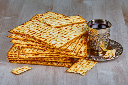 yiddish: Closeup of Matzah with cup of wine on wooden table