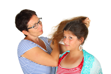 jewess: woman brushing her daughters hair against a white background