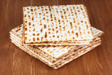 dinners: matzo on wooden table which is the unleavened bread served at Jewish Passover dinners
