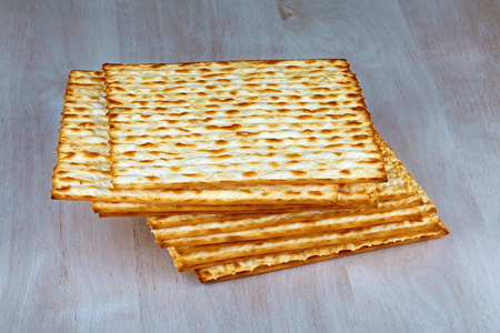 matzo: Closeup of Matzah on wooden table which is the unleavened bread served at Jewish Passover dinners Stock Photo