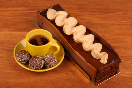 chocolate cake with cup of coffee and chocolate balls on  wooden table Stock Photo
