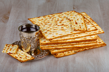 pesakh: Closeup of Matzah with kiddush cup of wine on wooden table