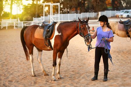 Jeune fille dans l'écurie à cheval