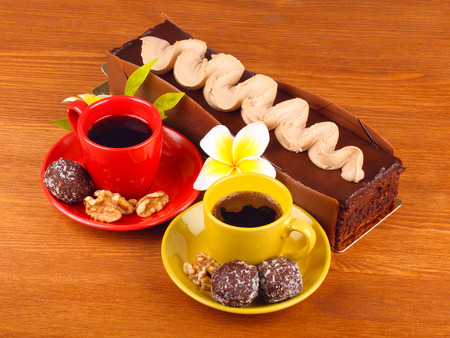 gateau: chocolate cake with two cup of coffee and chocolate balls on wooden table