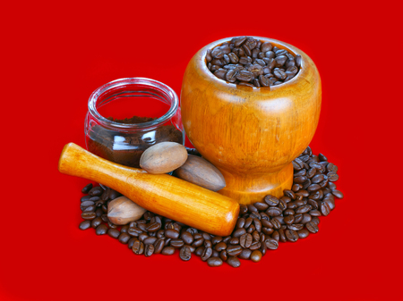 Mortar and pestle with black coffee and coffee beans on red background