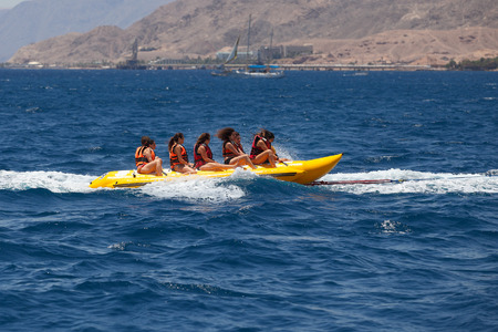 resort life: Eilat, Israel - JUNE, 23, 2017: Sea attraction, Group of young enjoying a ride on a banana boat on sunny summer day. Beach water sport Editorial