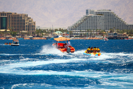 Eilat, Israel - JUNE, 23, 2017: Sea attraction, Group of young enjoying a ride on a banana boat on sunny summer day. Beach water sport Sajtókép