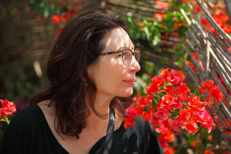 middle aged woman sniffing a tropical flowers in the garden