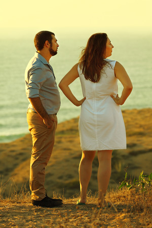 young couple standing on the beach and gaze into the distance together.
