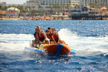 Eilat, Israel - JUNE, 24, 2017: Sea attraction, Group of young enjoying a ride on a banana boat on sunny summer day. Beach water sport Editorial