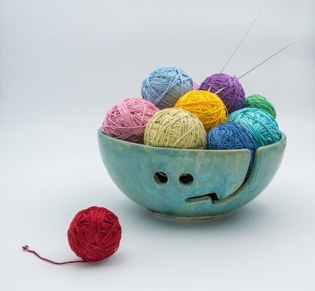 Skeins of yarn and knitting needles in a ceramic bowl