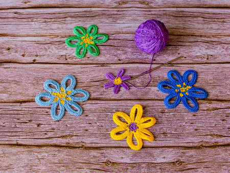 Crocheted flowers and ball of violet yarn on wooden background