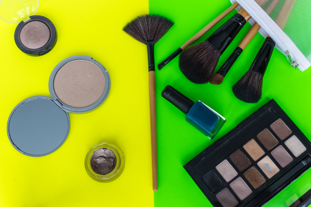 Overhead view of make up products spilling out of a pastel blue cosmetics bag, on to a bright yellow and green background