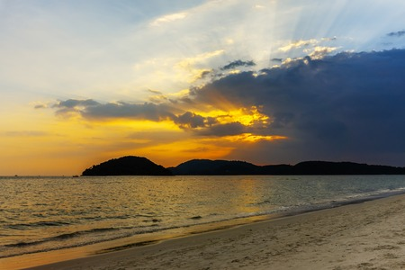Landscape of colorful sunset on paradise tropical island beach. Dramatic sunset with cloudy sky. Imagens