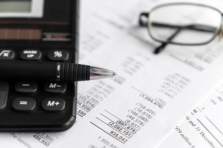 Investimento e analisi del foglio di rendiconto finanziario e concetto di reporting con calcolatrice, vetro e penna. messa a fuoco selettiva.