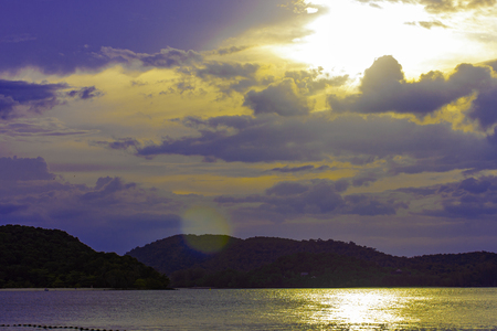 Background with Summer sunset on sea. The setting sun shining in a cloudy sky, Asia region.