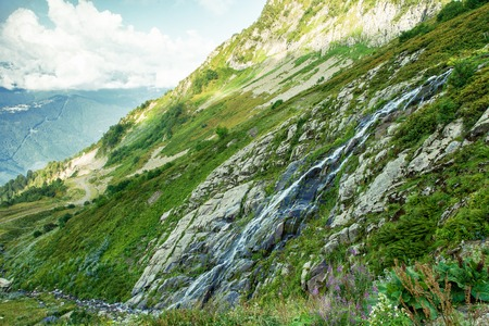 Caucasus Mountain waterfall at mountain valley background. Waterfall mountain valley landscape