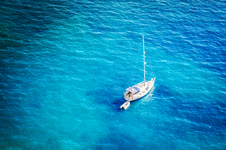 Aerial view of yacht in beautiful blue lagoon at hot summer day. Top view of sailing boat ready for cruise.