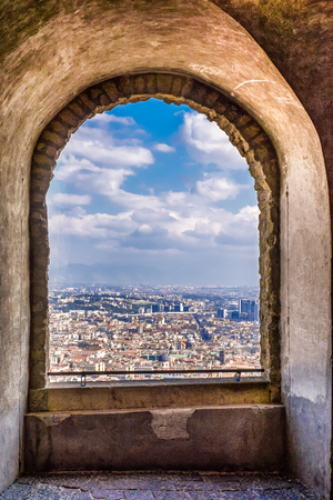 Arch view to the city from ancient castle in Naples, Italy, Castel Sant'Elmo. Cityscape and ancient architecture concept