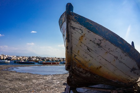 Old wooden abandoned fishing boat on the shore in Italy