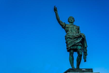 Roman emperor bronze statue on blue sky background, Europe