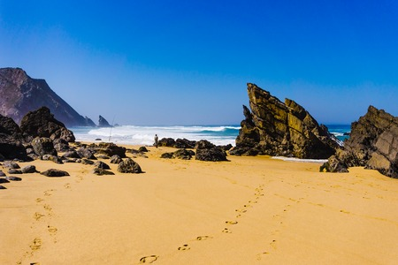 Sandy Adraga beach between rocks coastline of Atlantic ocean, Portugal Atlantic coast