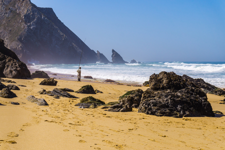 Atlantic ocean rocky coastline of sandy Adraga beach with fisherman. Portugal rocky coast