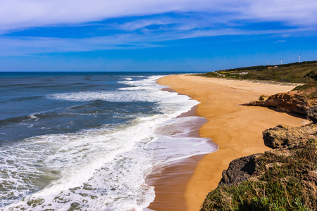 Foamy Atlantic ocean wave on deserted Nazare beach surrounded by green hills, Portugal.