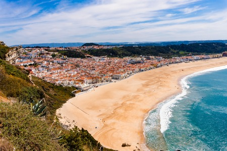 Wonderful romantic afternoon panoramic landscape coastline of Atlantic ocean. View Nazare beach riviera, Praia da Nazare, with cityscape of Nazare town in low season at sunny weather. Portugal.