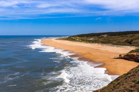 Foamy Atlantic ocean waves on deserted Nazare beach surrounded by green hills, Portugal.