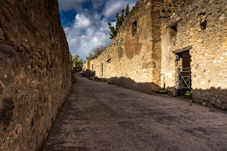 Ancient paved street is recovered in the middle of Roman ruins in Pompeii, Italy. Popular tourist destination.