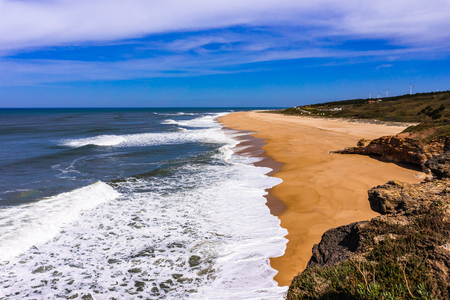 Empty long Nazare sandy beach with cliff Atlantic Ocean, Nazare, Portugal