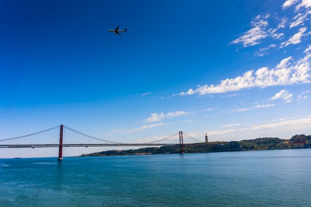 Cityscape with 25 April Bridge over the Tagus river and airplane in Lisbon in Portugal