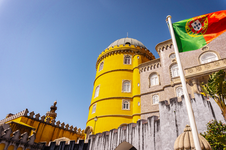 Palace of Pena in Sintra and Portuguese flag waving in the wind. Lisbon, Portugal.