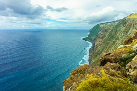 Rocky coast of the Atlantic ocean at Madeira archipelago in Portugal at cloudy day. Mountains, rocks and ocean. Zdjęcie Seryjne