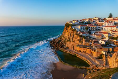 Typical portugese village Azenhas do Mar on top of oceanic cliffs at sunset, Portugal Stock Photo