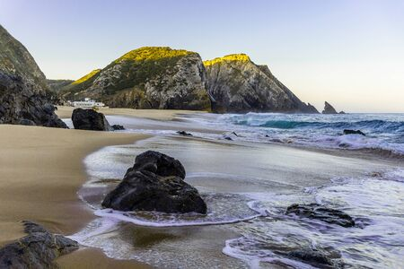 Rocky beach at sunrise, Portugal. Counter light. Travel and business background