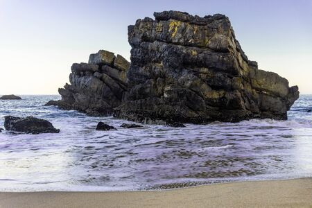 Beautiful sandy beach with rocks on Atlantic coast and waves of ocean, Adraga beach, Portugal