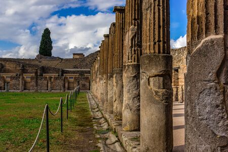 Pompeii ruins: stone columns at archeological site. Remains of the ancient Pompeii town destroyed by eruption of volcano Vesuvius, Italy