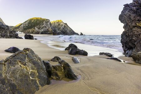 Rocky beach at sunrise, Atlantic ocean coast, Adraga, Portugal. Travel and business background