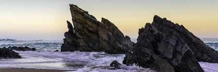 Amazing cliff rocks on the west coast of Portugal on Adraga beach at sunrise. Wide banner. Stock fotó