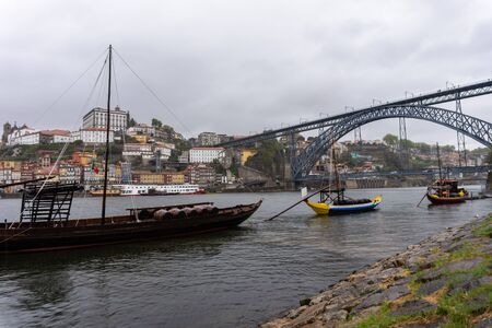 Porto at rainy day, Portugal old town cityscape on the Douro River with traditional Rabelo boats with barrels of port wine. 写真素材