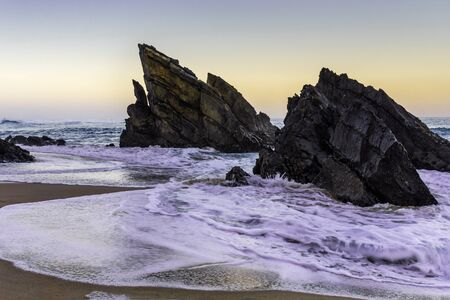 Amazing cliff rocks on the west coast of Portugal on Adraga beach at sunrise
