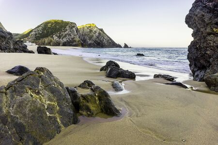 Sandy beach with rocks on Atlantic coast and waves of ocean, Adraga beach, Portugal