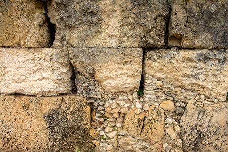 Masonry wall of old stone blocks of limestone. texture